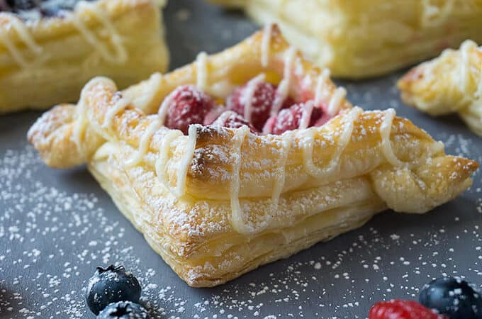 There are so many different textures going on in these pastries: buttery, flaky layers that are so light and airy with crispy, crunchyedges. Tart, juicy berries nestled ina rich, creamy, sweet filling. Each bite is delightful!