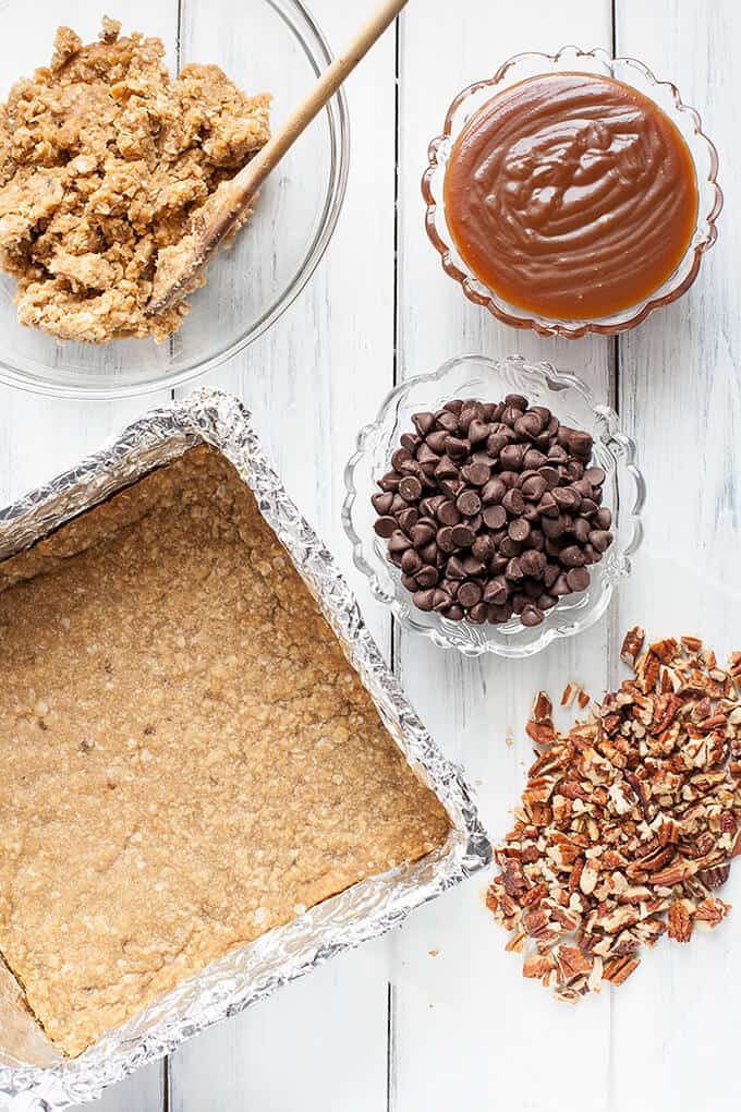 Chewy, gooey Salted Caramel Oatmeal Carmelitas- pockets of gooey, salted caramel oozing out from in between chunks of chocolate and crunchy pecans, all nestled in a brown sugar, oatmeal cookie crust and topped with anoatmeal streusel topping - Caramel Euphoria!