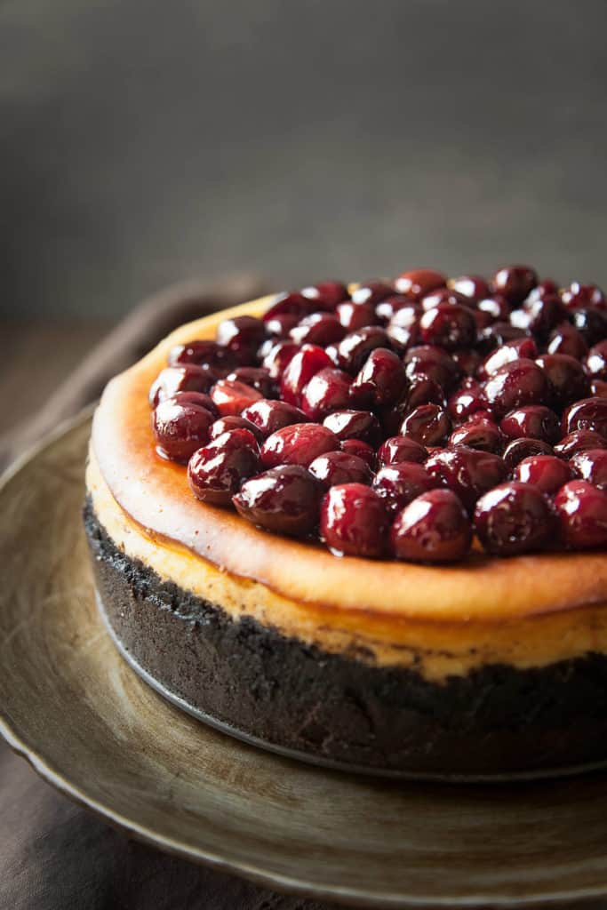 Classic New York Cheesecake with a Chocolate Cookie Crust and Roasted Cherries is a heavenly cloud of silky perfection. Rich, creamy, and ethereally light.
