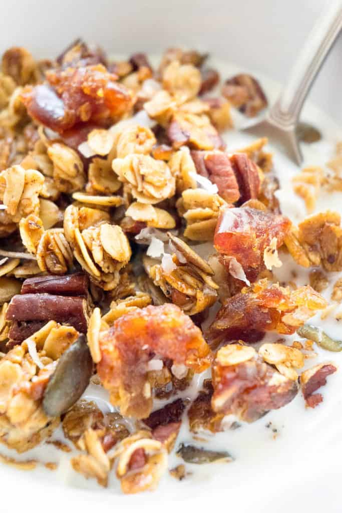 Crunchy clusters of maple sweetened granola with whole rolled oats, pecans, dates, pepitas, coconut and warm pumpkin spice. Healthy, delicious, and so easy to make!