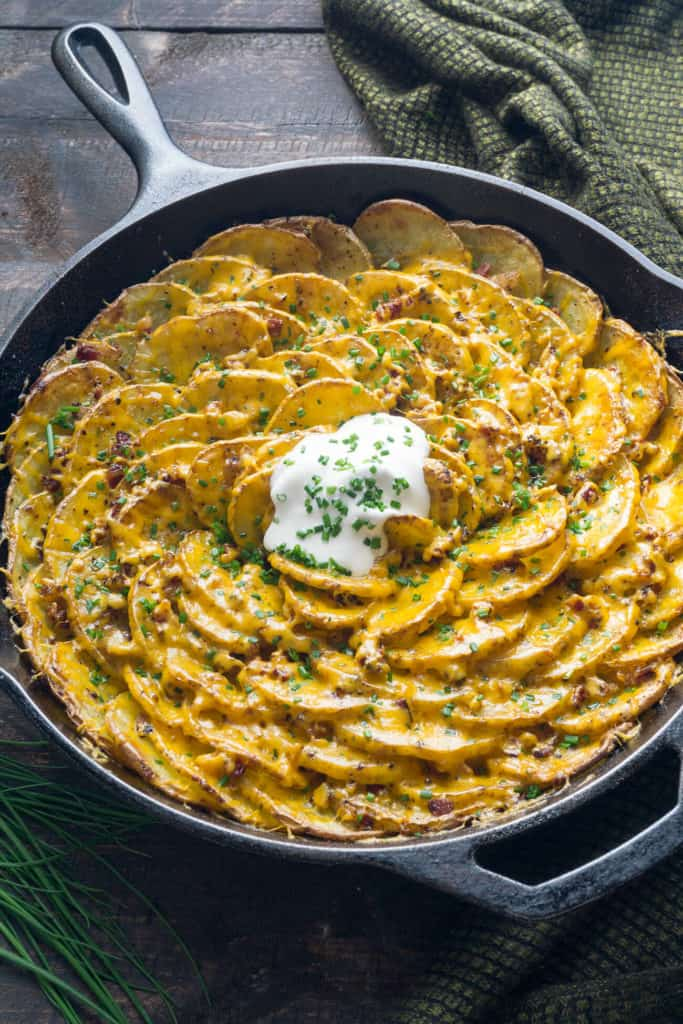 Bacon and Cheddar Spiral Loaded Roasted Potatoes are arranged in a vertical spiral for maximum crispness, roasted with bacon tucked into every little crevice, then topped with cheddar, chives, and sour cream. The BEST potato dish!