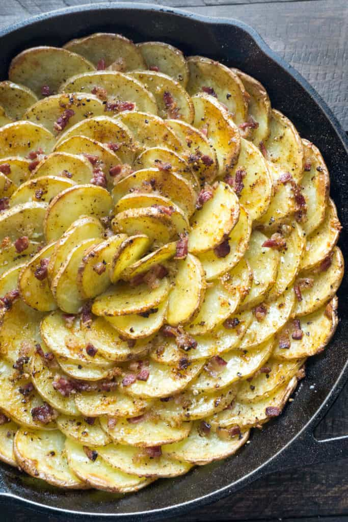 Spiral Roasted Potatoes - Potato slices tossed with lots of garlic, arranged in a vertical spiral for maximum crispness, roasted with bacon tucked into every little crevice. The BEST way to cook potatoes!