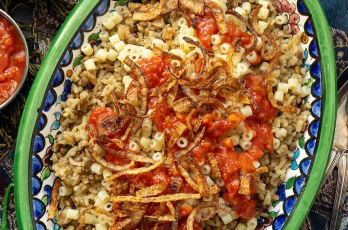 Kushari is Egyptian comfort food at its finest. With cumin scented lentils and rice topped with pasta, a spicy, vinegary tomato sauce, and crispy fried onions, Kushari is a real carb fest - and it's totally addictive!