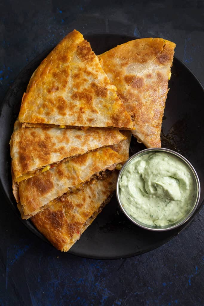 A crispy tortilla filled with refried beans, melted cheddar and Monterey jack cheeses, sweet corn, red bell pepper, and juicy, Mexican-spiced ground beef - these Beefy Bean and Cheese Quesadillas are a family favorite. If only restaurant quality was this awesome! Added bonus - they are super quick and easy to make.