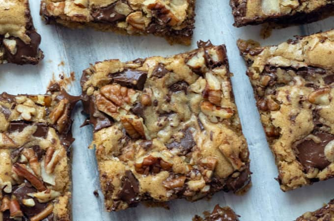 Chewy Chocolate Chunk Blondies are rich and chewy with a hint of butterscotch flavor and packed with chocolate chunks and roasted pecans. Super quick and easy to make, they mix up by hand in just one bowl. A family favorite!