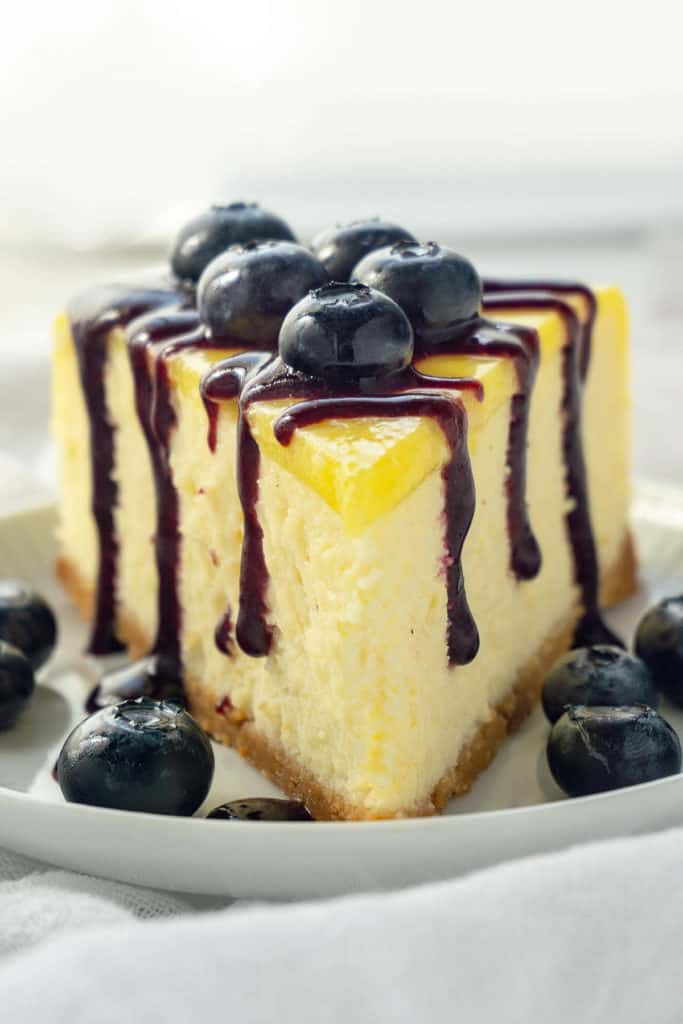 Luscious Lemon Blueberry Cheesecake - rich and creamy lemon cheesecake with a sweet shortbread crust, topped with lemon curd and a vibrant blueberry sauce. Melt-in-your-mouth creaminess and silky smooth. Pure deliciousness!