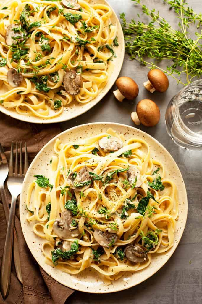 Creamy, Cheesy Mushroom Spinach Pasta - sautéed mushrooms and baby spinach tossed with buttered fettucine in a garlicky, parmesan cream sauce. So delicious and so quick and easy to make! This dish is all flavor. You've got to love a restaurant quality meal that's ready in under 30 minutes.