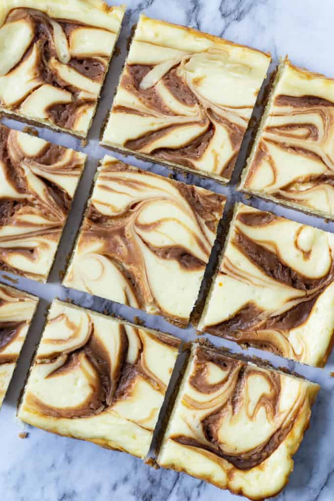 Swirled Caramel Cheesecake Bars - rich, creamy, and velvety smooth cheesecake on top of a sweet, crunchy, shortbread crust, with swirls of rich caramel. All the deliciousness of cheesecake in a quick and easy bar! #cheesecake #cheesecakerecipe #cheesecakebars #bars #caramel #dessert #quick #easy #cheesecakerecipes