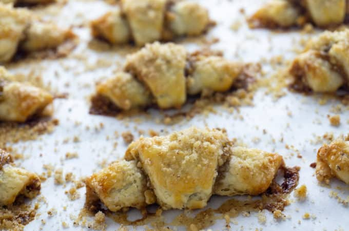 Rugelach, tiny crescent shaped pastries, are afamily favorite. A tender, flaky, cream cheese dough is wrapped around afilling of apricot jam, brown sugar, and walnuts. #rugelach #cookies #cookierecipes #recipes #holidayrecipes #holidaydesserts #holidaycookies