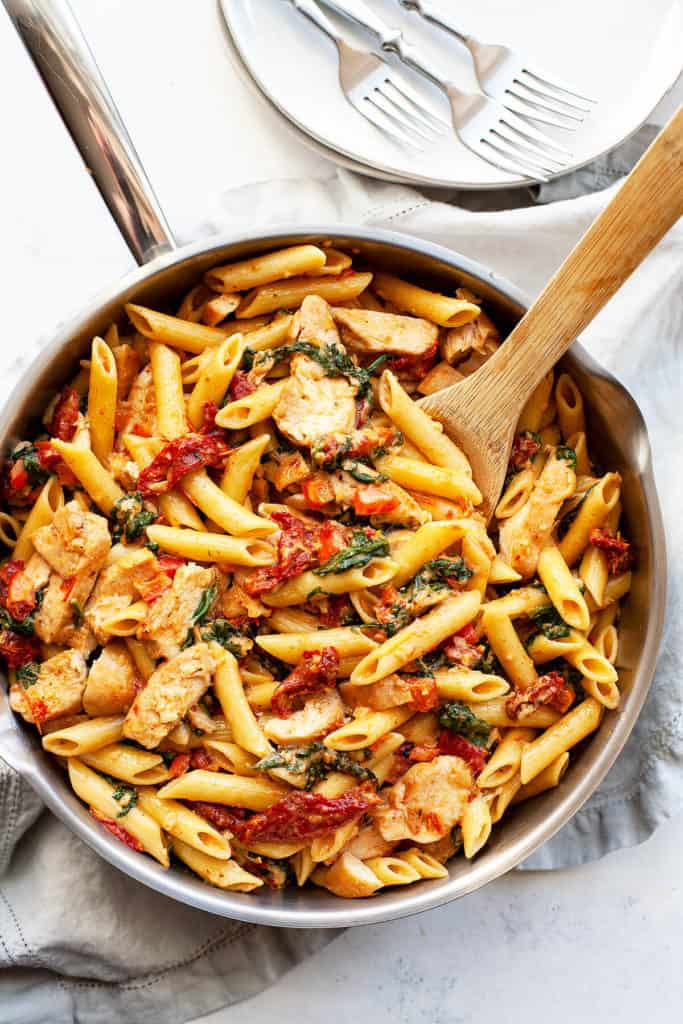 Creamy Tuscan Chicken Pasta is loaded with the flavors of the Mediterranean – sundried tomato, baby spinach, garlic, red pepper, and parmesan. It's super quick and easy. A restaurant quality dish on the table in under 30 minutes. #pasta #recipe #recipeeasyfast #chicken #chickenrecipes #chickendinner #chickendishes #easy #easyrecipe #easydinner