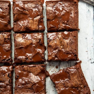 These Ultimate Fudgy, Chewy Brownies are dense, moist, and intensely chocolatey with a crackly top and puddles of molten chocolate. Somewhere between a rich truffle torte and a piece of fudge, their chewy texture is absolute perfection. #brownies #dessert #fudgy #chewy #chocolate #best #easy