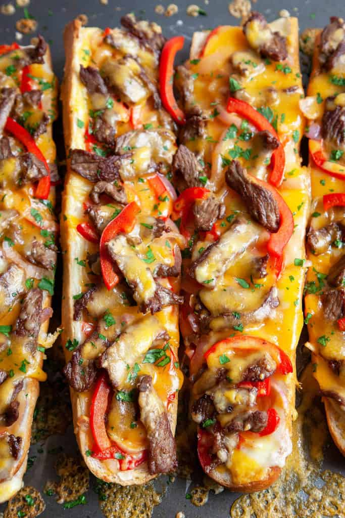 Melty cheese, strips of juicy steak, and sautéed peppers and onions, toasted on top of crusty French bread, this Cheesy Philly Cheesesteak Bread is a cross between a Philly Cheesesteak and a French bread pizza. Perfect for gameday, appetizer, snacking, or an easy dinner. Quick, easy, delicious. #phillycheesesteak #philly #cheesesteak #steak #pizza #frenchbread #cheese