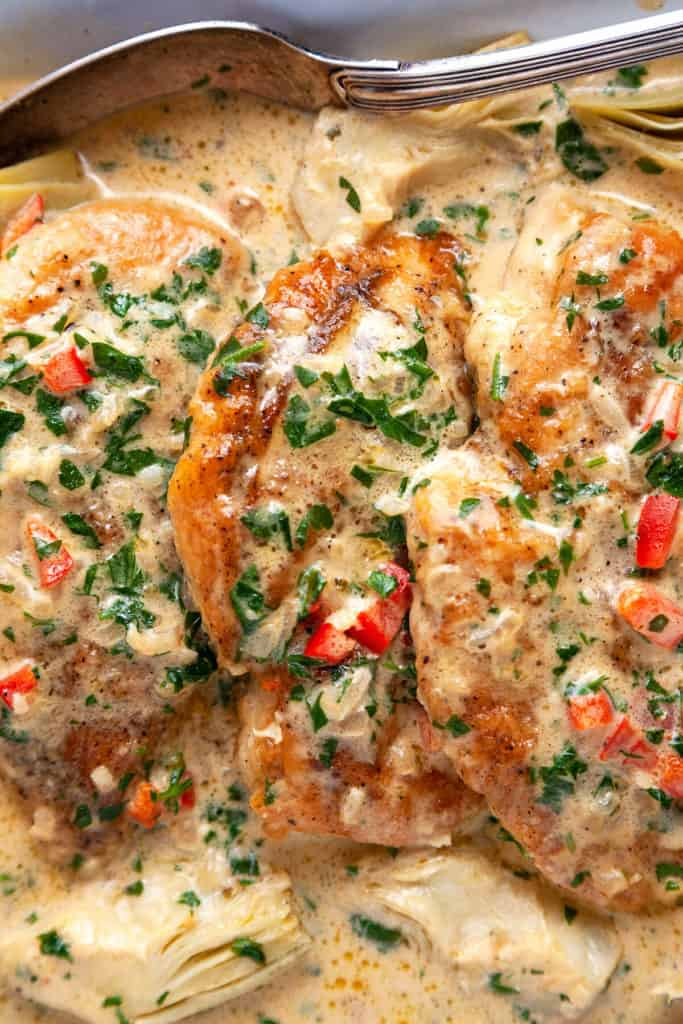 These Creamy Artichoke Chicken Breasts are irresistible! Sautéed chicken breasts are in a lemony, garlicky parmesan cream sauce with artichokes, red peppers, and parsley. On the table in 15 minutes. Quick, easy, delicious. #chicken #chickenbreasts #chickendinner #quick #easy #under30minutes #recipe #lowcarb #keto