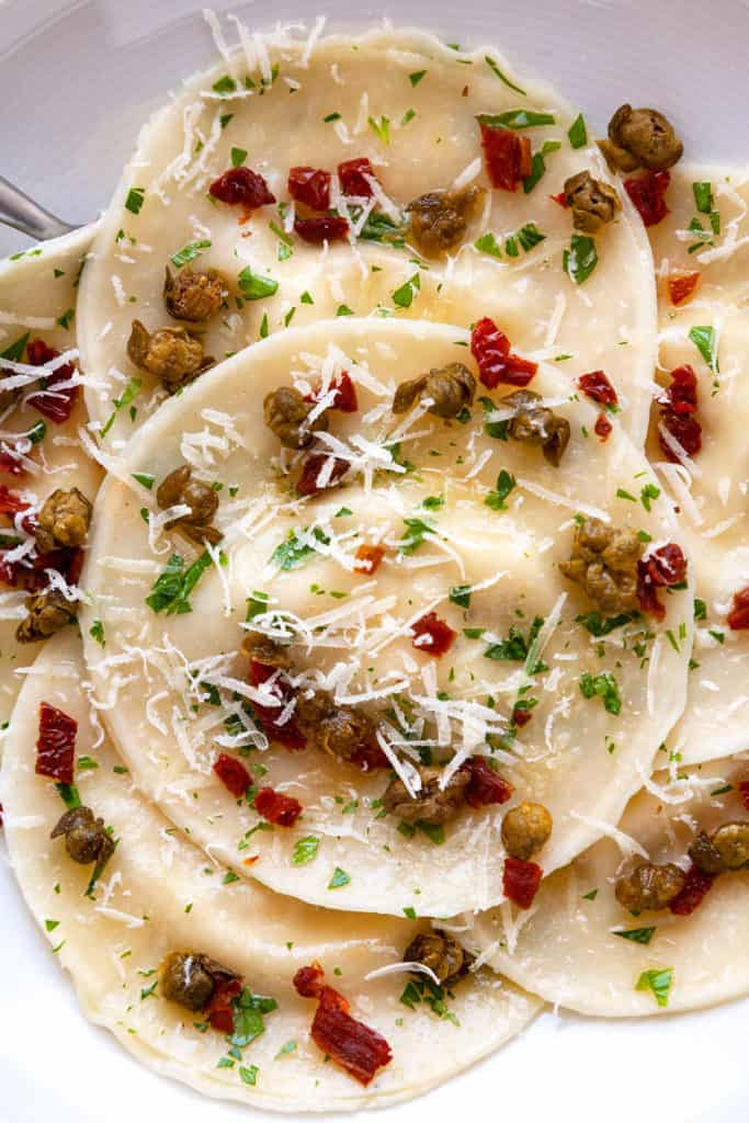 This Easy Artichoke Ravioli is full of the flavors of the Mediterranean! Ravioli is stuffed with lemony, marinated artichokes, creamy ricotta, and parmesan. It's tossed in a simple parsley butter with sun dried tomatoes and fried capers sprinkled on top. Made quick and easy using dumpling wrappers (gyoza). #ravioli #pasta #gyoza #dumplingwrapper #wonton #italian #artichoke #sundriedtomato #capers #easy #dinner