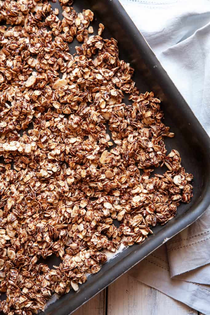Double Chocolate Granola - crunchy chocolate oat clusters, sliced almonds, flakes of coconut, and best of all – a decadent chocolate coating. Sprinkled with raw sugar for even more crunch. Chocolate for breakfast? Yes, please! #granola #recipe #chocolate #cocoa #breakfast #easy #quick
