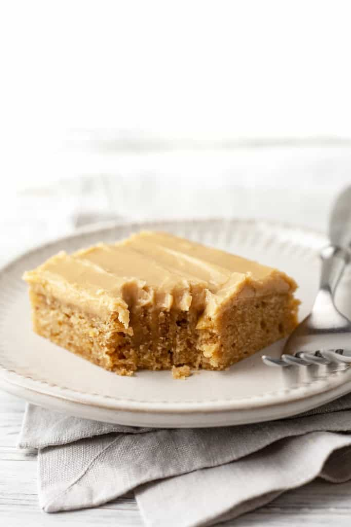 These Banana Blondies are dense yet soft, moist, and full of sweet banana flavor. Topped with a creamy, caramely brown sugar frosting, they're irresistible! #recipe #easy #dessert #sweet #banana #frosting #blondies #brownsugar #bakesale #potluck #best