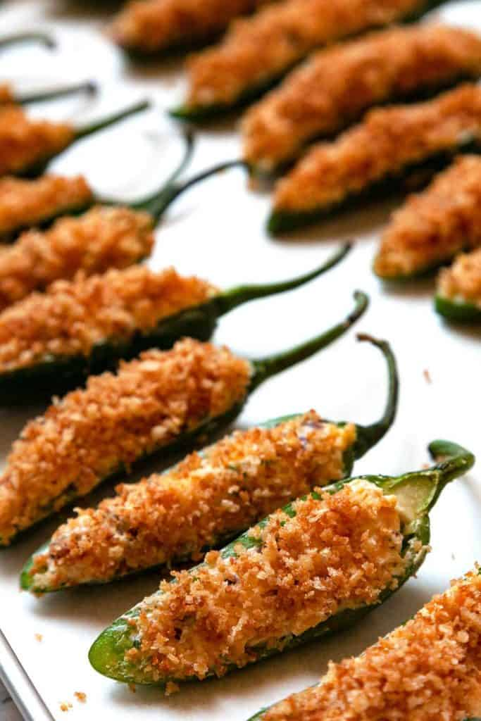 Jalapeno Poppers are a game day favorite! Fresh jalapenos filled with a creamy cheese and bacon filling, topped with crispy panko, and baked to golden-brown crispy perfection. #jalapeno popper #recipe #easy #baked #bacon #video #cheddar #cream cheese #vegetarian #best #stuffed #oven #healthy #appetizers #party #game day