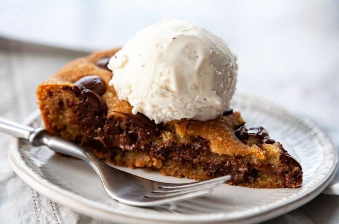 Nutella-Stuffed, Deep Dish, Chocolate Chip Skillet Cookie - A crispy, chewy, buttery chocolate chip cookie on the outside and an irresistible, ooey-gooey Nutella-stuffed center, baked in a cast iron pan. Serve warm from the oven with vanilla ice cream for the ultimate dessert! #skilletcookie #castiron #easy #chocolatechip #withpremadedough #videos #recipe #gooey #stuffed #nutella #giant #best #sundae #homemade #deepdish #12inch #10inch #individual