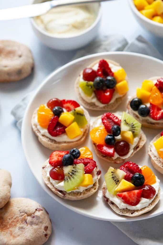 Mini Fruit Pizzas with fresh juicy fruit, velvety smooth cream cheese, and a soft, chewy crust. A delicious and healthy snack your whole family will love! Quick and easy to make with wholesome ingredients you can feel good about serving.