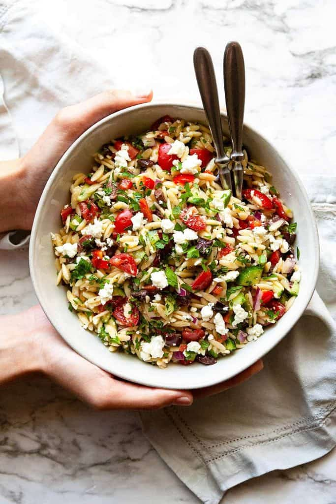 Quick and easy to make Greek Orzo Salad is loaded with fresh crunchy veggies and all of your favorite Mediterranean flavors. This healthy pasta salad recipe is perfect for picnics, potlucks, or barbeques or as an easy, flavorful side dish for dinner.