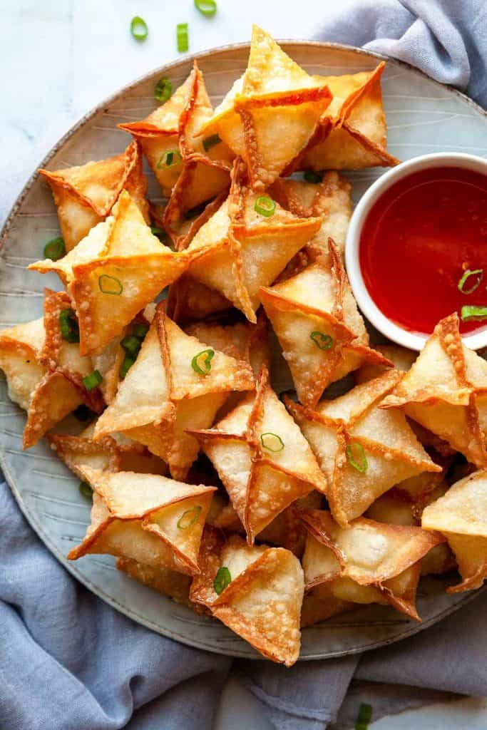 The BEST Crab Rangoon - A lush and creamy crab and cream cheese filling in a crispy wonton – the perfect party appetizer or game day snack recipe! With instructions for frying, baking, or air frying, they're easy to make and always a hit!