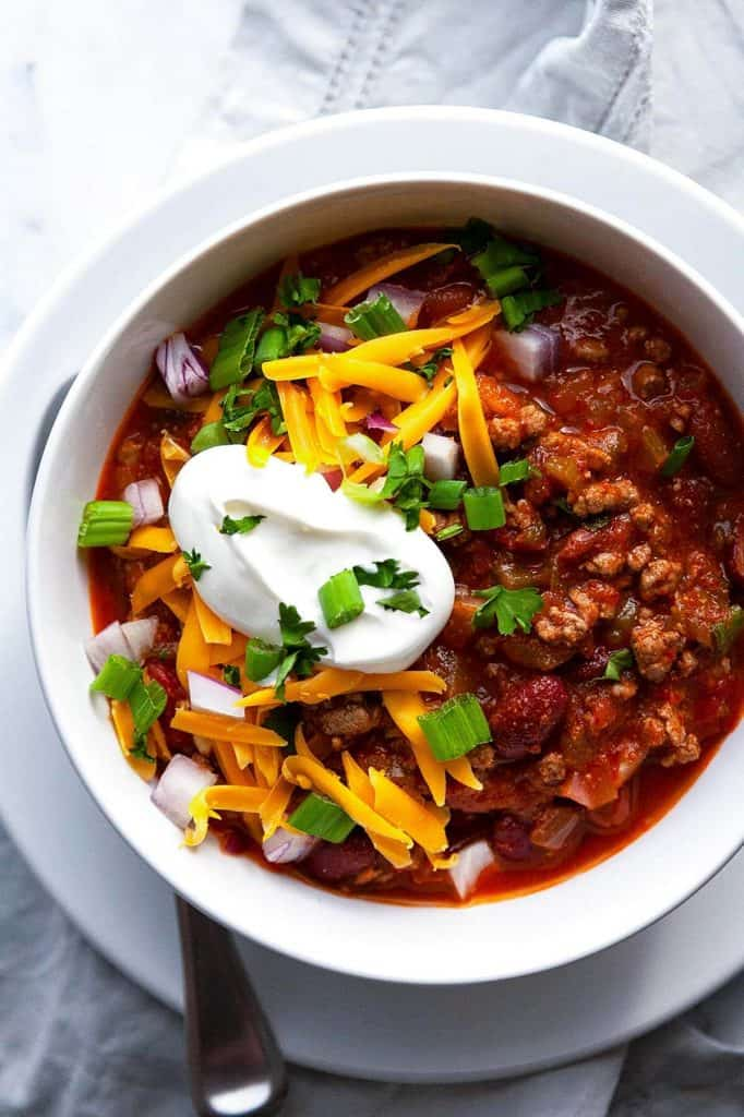The best classic Chili recipe, ready in 30 minutes! Loaded with ground beef, tender beans, tomatoes, and a simple homemade blend of chili seasoning, piled high with all of your favorite toppings. So much flavor!