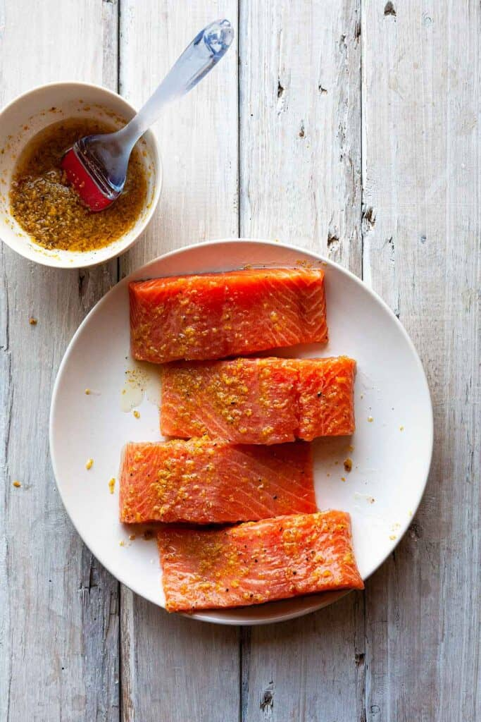 raw salmon fillets brushed with lemon pepper marinade