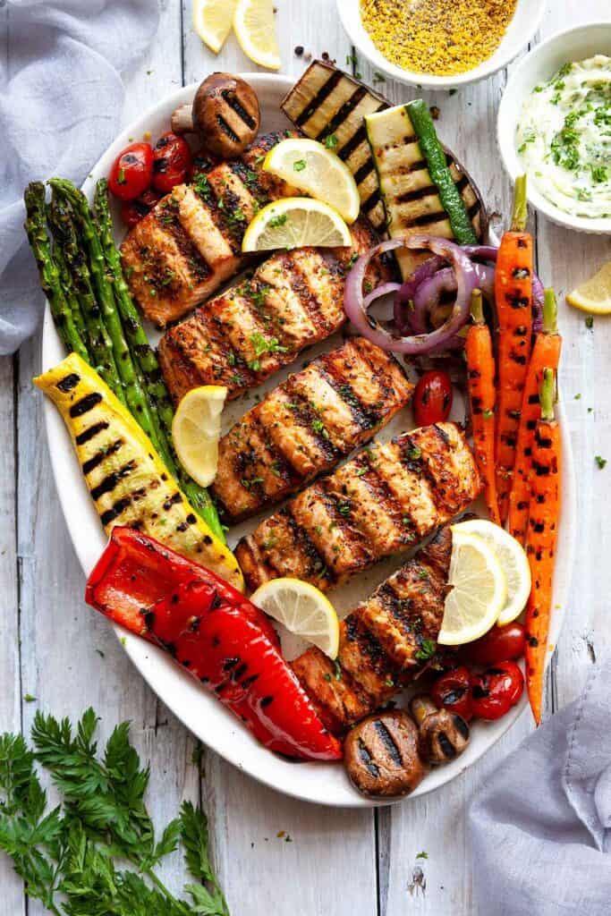 grilled salmon on a platter with grilled vegetables