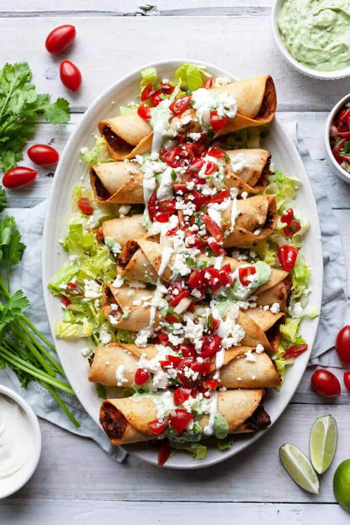 plate of chicken flautas on a bed of lettuce topped with avocado crema, sour cream, and pico de gallo