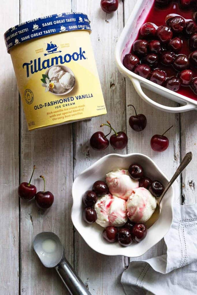 Tillamook ice cream in container, a dish of roasted cherry sauce, and a bowl of ice cream with cherry sauce