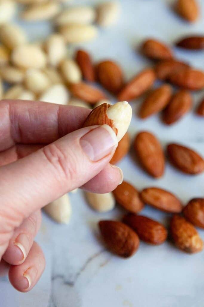 photo of a hand squeezing the skin off of a whole almond