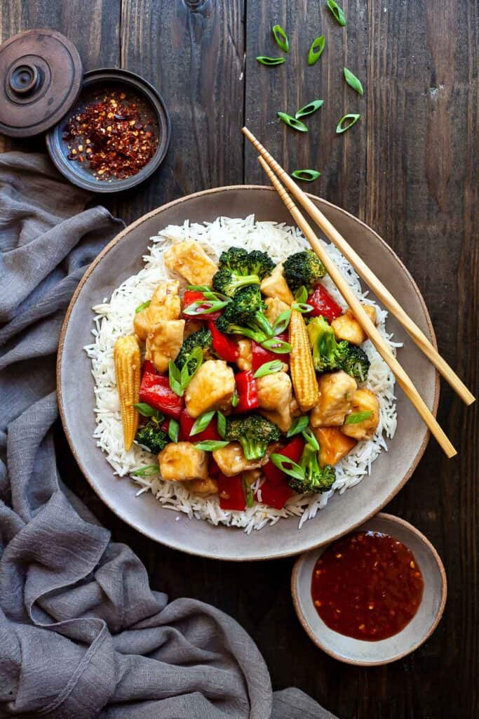 a dish of Hunan chicken with rice and chopsticks