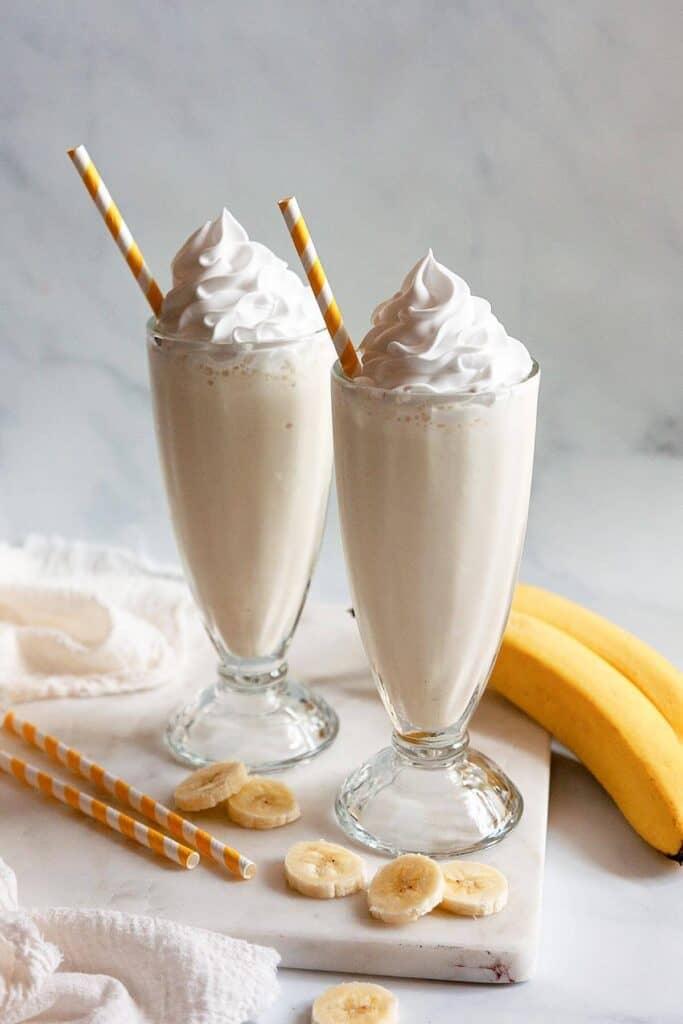 two banana milkshakes in old fashioned milkshake glasses
