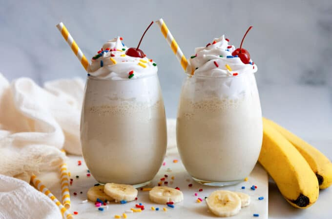 two banana milkshakes topped with sprinkles and cherries
