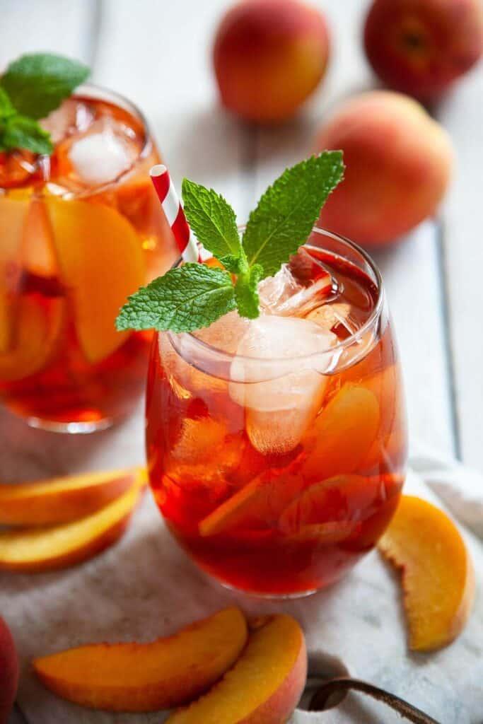 glasses of peach iced tea and peaches