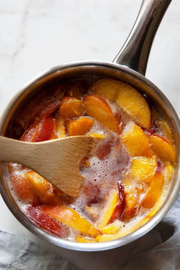 sliced peaches, sugar, and water cooking in a pan to make peach syrup