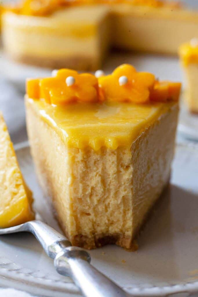 a slice of mango cheesecake with a bite taken out