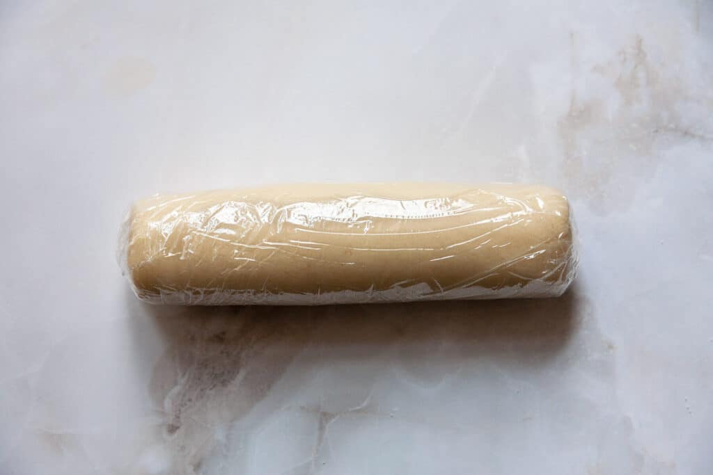 a log of almond paste wrapped in plastic